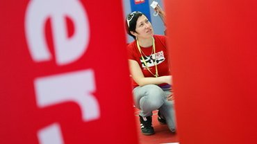 Frau sitzt hinter ver.di-Logo