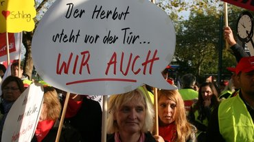 Frau trägt Schild: Herbst steht vor der Tür - Wir auch!