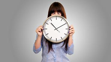 Junge Frau hält eine Uhr vor sich und schielt aufs Zifferblatt.