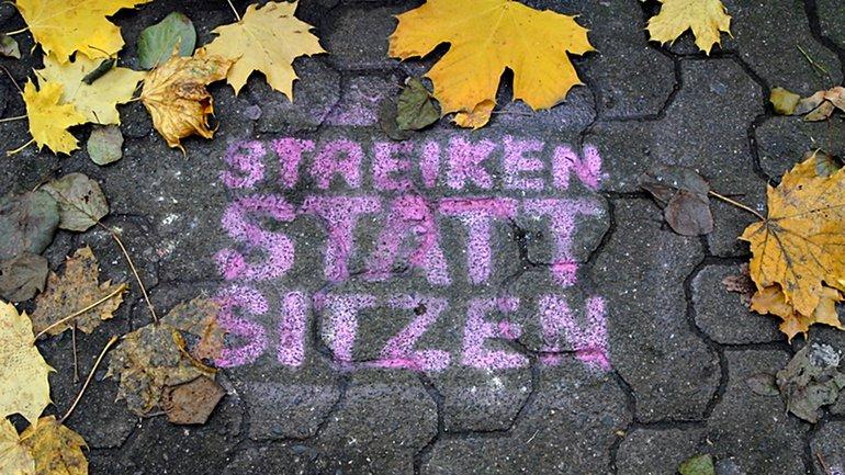 Streik Streiken statt sitzen Schriftzug Graffiti
