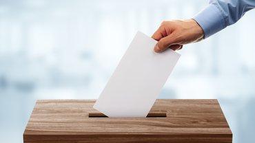 Jemand gibt seinen Stimmzettel an der Wahlurne ab