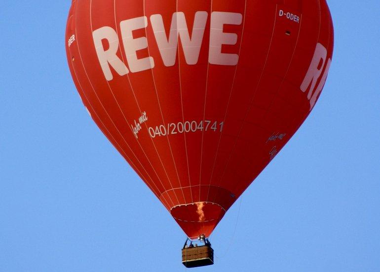 Ein Ballon fliegt Werbung für Rewe