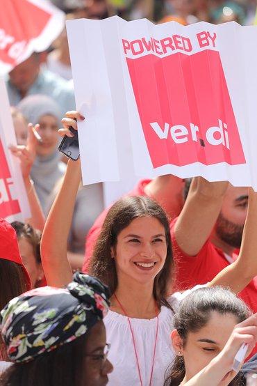 "junge, lachende Frau mit Plakat ""powered by ver.di"""