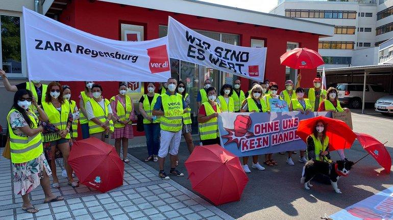 Mit Schirm, Charme und Streikhund: Beschäftigte von Zara und Norma am 22. Juli 2021 in Regensburg